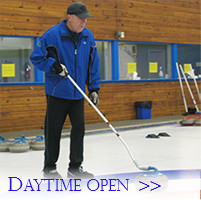 A senior curler uses a stick to deliver a stone